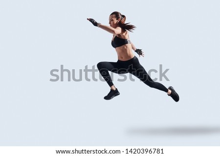 Motivated to shape her body. Full length of attractive young woman in sports clothing exercising while hovering against grey background #1420396781