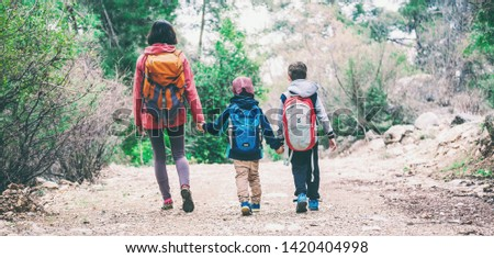 A woman with two children goes through the forest. The boy walks in the park with his mother and brother. Family holiday. Brunette with a backpack travels with children. Mom holds sons hands. #1420404998