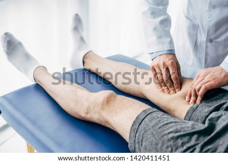 partial view of Physiotherapist massaging leg of man on massage table in hospital #1420411451