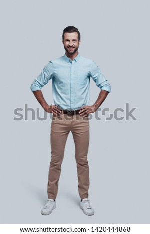 Confidence and charisma. Full length of handsome young man looking at camera and smiling while standing against grey background #1420444868