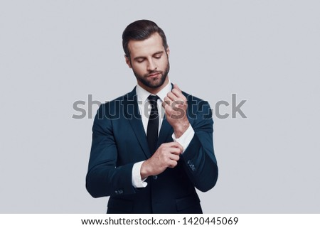 Confidence and charisma. Handsome young man adjusting his sleeve while standing against grey background #1420445069