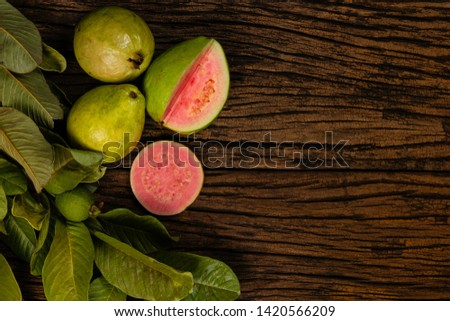 Fresh red guavas with green leaves on wooden demolition background. Wood texture and guava leaves. #1420566209