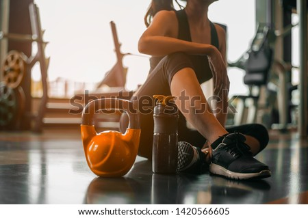 fitness ,workout, gym exercise ,lifestyle  and healthy concept.Fitness woman Relaxing after exercise with a whey protein and dumbbell placed beside the gym.Relaxing after training. #1420566605