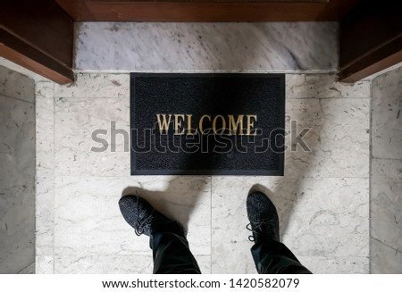 A man standing on top of a welcome floor mat in front of an apartment door