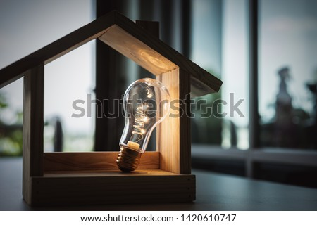 Light bulb with wood house on the table, a symbol for construction, Creative light bulb idea, power energy or business idea concept ecology, loan, mortgage, property or home. #1420610747