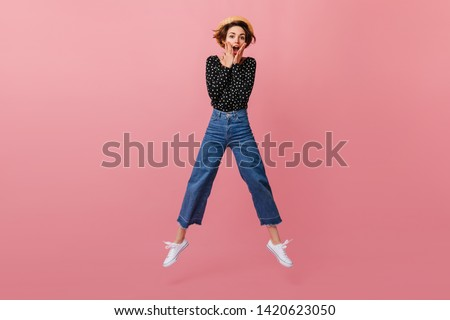 Funny girl in straw hat jumping on pink background. Studio shot of emotional woman in vintage jeans dancing and looking at camera. Royalty-Free Stock Photo #1420623050