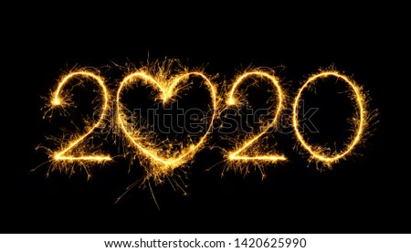 Happy New Year 2020. Creative Number 2020 with sign heart written sparkling sparklers isolated on black background for design. Beautiful Glowing overlay template for holiday greeting card. #1420625990