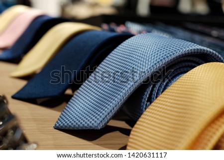 selective focus at blue necktie. Roll up necktie on the table and blur background . Concept of gentleman and necktie fashion, Shopping , father's day. #1420631117