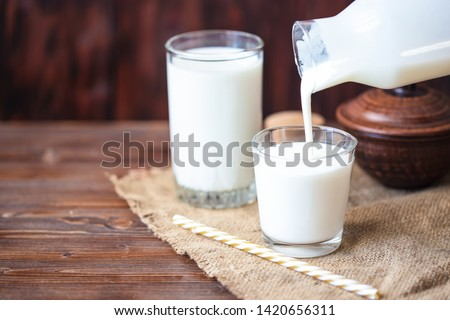 Pouring homemade kefir, yogurt with probiotics Probiotic cold fermented dairy drink Trendy food and drink Copy space Rustic style. #1420656311