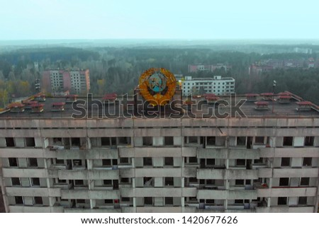 Pripyat aerial panorama cityview over the sign of USSR on the roof of building. Drone flies over the deserted abandoned city of Pripyat, Ukraine. Exclusion zone near the Chernobyl nuclear power plant. #1420677626
