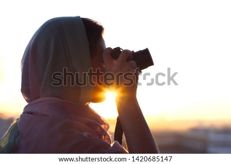 Arab Woman Photographer in a scarf taking picture using Camera on the sunset background. Halal travel concept