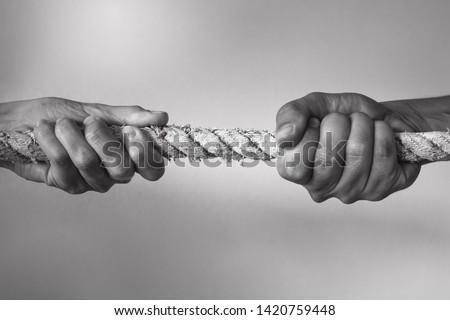 Hands pulling rope playing tug of war, people competitive, dispute, contest concept.  #1420759448