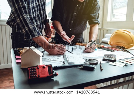 Engineer and contractor planning projects together at desk with blueprints. #1420768541