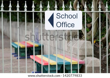 School office direction arrow sign in playground