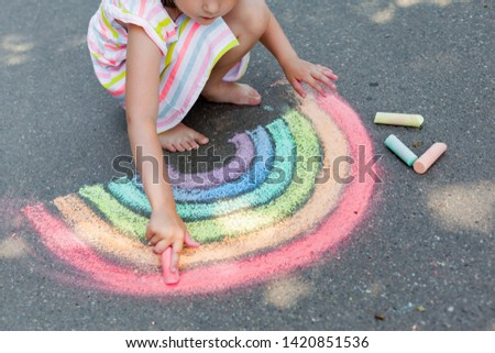 Kids paint outdoors. Portrait of a child girl drawing  a rainbow colored chalk on the asphalt on summer sunny day. Creative development of children
