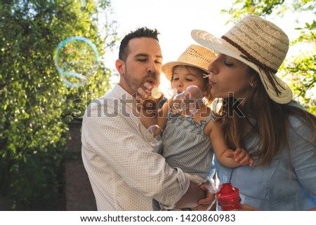 Happy Hispanic Family Having Fun Together Outdoors. Lovely Family Spending Time Together in the Park. Cute Spanish Couple Playing with Bubbles . Family Concept. #1420860983