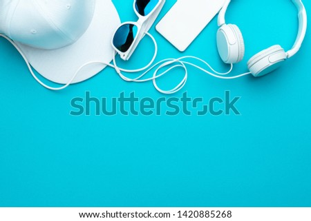 Flat lay image of modern teenager accessories background - headphones, sunglasses, smartphone, baseball cap. Top view of white accessories on turquoise blue background with copy space #1420885268