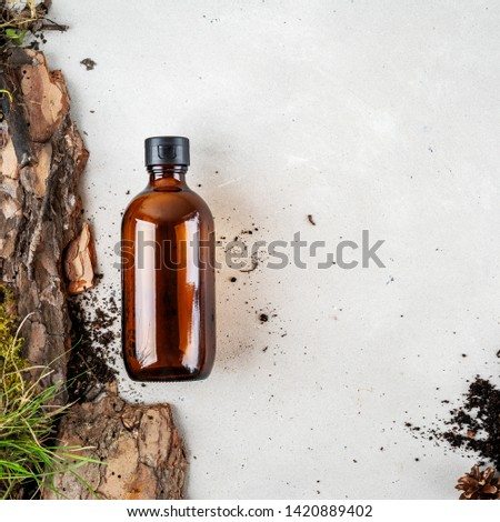 One brown glass Mock up bottles of shampoo  over Natural background of real tree bark, tiny mosses and grass organic with copy space. Flat lay.  #1420889402
