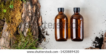 Two brown glass Mock up bottles of body care cosmetics over Natural background of real tree bark, tiny mosses and grass organic for cosmetic products with copy space. Flat lay. Long wide banner #1420889420