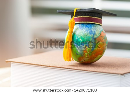 Education to learn study in world. Graduated student studying abroad international idea. Master degree hat on top globe book. Concept of graduate educational for long distane learning anywhere anytime #1420891103