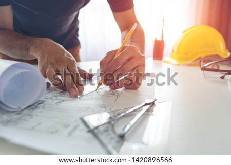 Construction engineer working at blueprint to build large commercial buildings at home #1420896566
