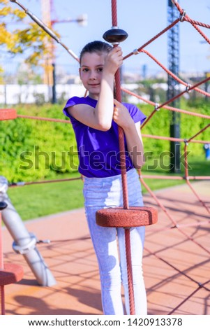Cute Girl with Long Hair is Enjoying in Summer Day and Playing in the Playground in the Public Park #1420913378