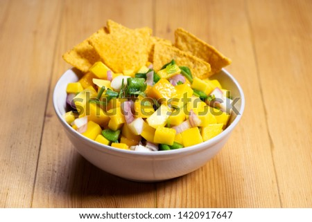 mango salsa salad with chips on wooden background #1420917647