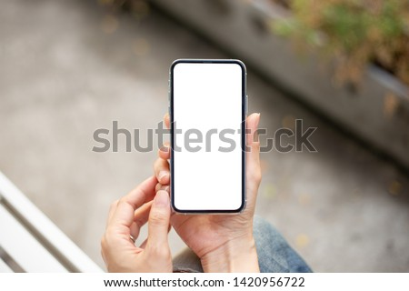 Mockup image screen cell phone.women hand holding texting using mobile at outdoor.copy space,white blank screen for text.concept for contact business,people communication,technology electronic device #1420956722