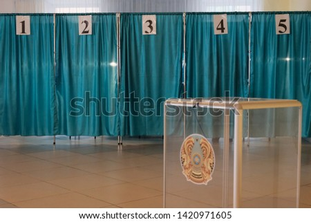 Kazakhstan, Qostanay, June 9, 2019, Qazaqstan,Individual booths with numbers in the voting room. Blue background. Transparent box with the emblem of Kazakhstan for counting votes. Close-up. #1420971605