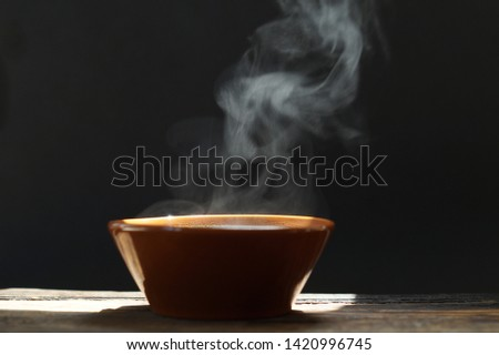 bowl of hot soup with steaming on wooden table on black background #1420996745