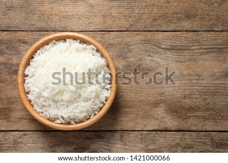Bowl of delicious rice on wooden table, top view with space for text #1421000066