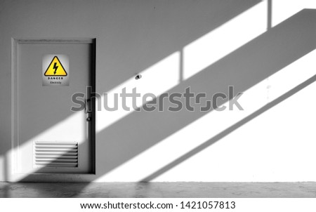 Sunlight and shadow on surface of gray wall and door of electrical control room with yellow warning sign in minimal style, exterior architecture concept