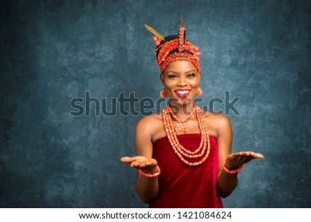 beautiful young nigerian woman wearing edo bridal attire stretching forward her open palms and smiling