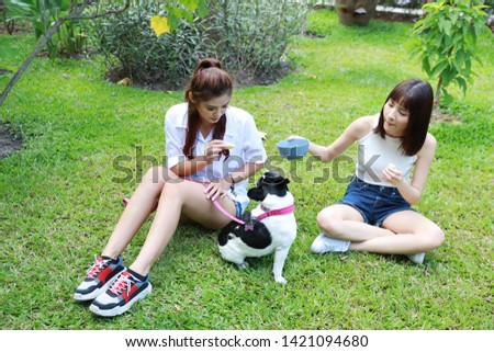 beautiful two young asian woman wearing white shirt who sitting on grass and playing with her cute dog with happy and smiling face in garden with green trees. (friendship concept) #1421094680