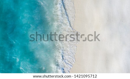 Summer seascape beautiful waves, blue sea water in sunny day. Top view from drone. Sea aerial view, amazing tropical nature background. Beautiful bright sea with waves splashing and beach sand concept #1421095712