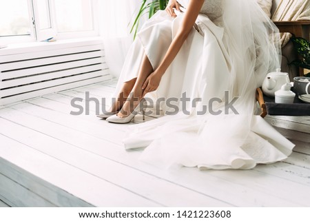 Bride dresses shoes before the wedding ceremony. Charges of the bride. Closeup detail of bride putting on high heeled sandal wedding shoes. Wedding bride shoes. Beautiful legs Royalty-Free Stock Photo #1421223608