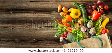 Beige canvas grocery bag with dark green handle fallen over while dropping vegetables and fruits on wood plank #1421290400