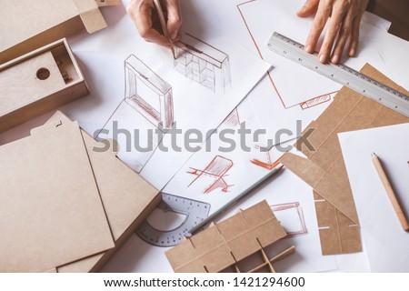Designer draws a mockup for crafting cardboard box. Development of packaging design sketch. #1421294600