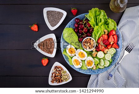 Plate with a paleo diet food. Boiled eggs, avocado, cucumber, nuts, cherry and strawberries. Paleo breakfast. Top view #1421294990