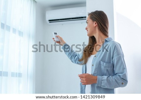 Young woman adjusts the temperature of the air conditioner using the remote control in room at home  Royalty-Free Stock Photo #1421309849