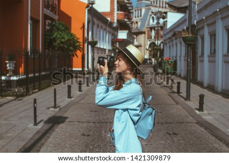 Photographer traveler in hat and with backpack takes pictures of sights while walking along the street of a european city. Vacation and travel holidays. Traveling lifestyle