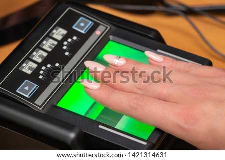 The process of scanning fingerprints during the check at border crossing. Female hand puts fingers to the fingerprint scanner. Biometric, identity verification and border control, immigration concept #1421314631