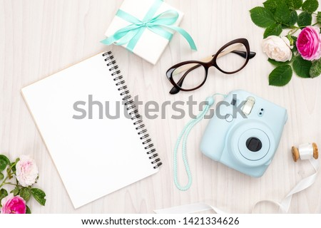 Modern polaroid camera, gift box, glasses, feminine accessories, roses on wooden background. Top view, tender minimal flat lay style composition. Women desk, fashion blogger, beauty technology #1421334626