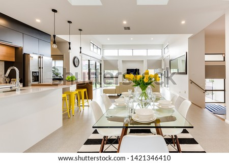 CANBERRA, AUSTRALIA – JUNE 6, 2018: Spacious kitchen furnished with chairs, table, stools, sink, island and large fridge extending into the lounge room in a modern home #1421346410