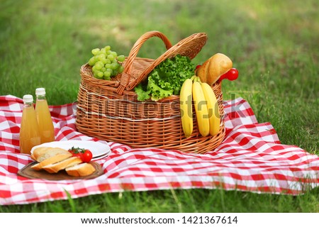 Wicker basket with food and juice on blanket in park. Summer picnic #1421367614