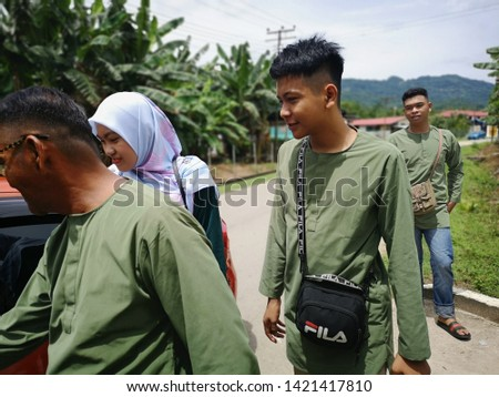 KOTA KINABALU, MALAYSIA- JUNE 4, 2019: Muslim friends and families visiting home and greet embrace each other celebrating eid mubarak. #1421417810
