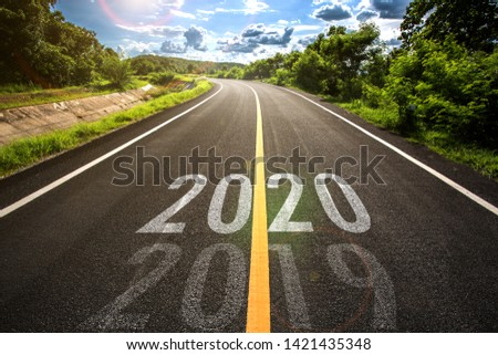 The word 2020 written on highway road in the middle of empty asphalt road at golden sunset and beautiful blue sky. Concept for new year 2020. #1421435348
