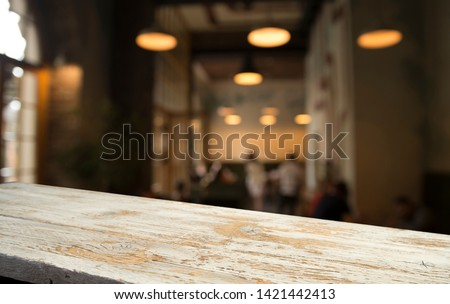 image of wooden table in front of abstract blurred background of resturant lights #1421442413