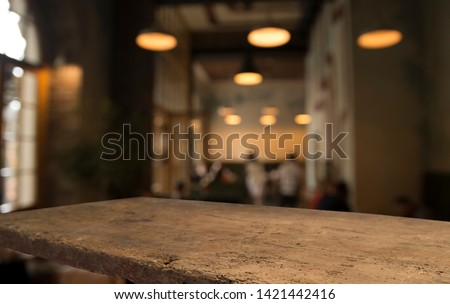 image of wooden table in front of abstract blurred background of resturant lights #1421442416