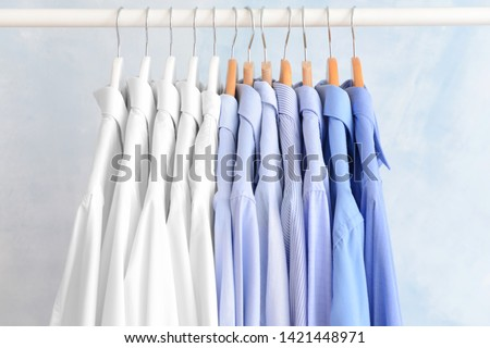 Rack with clothes after dry-cleaning on light background #1421448971
